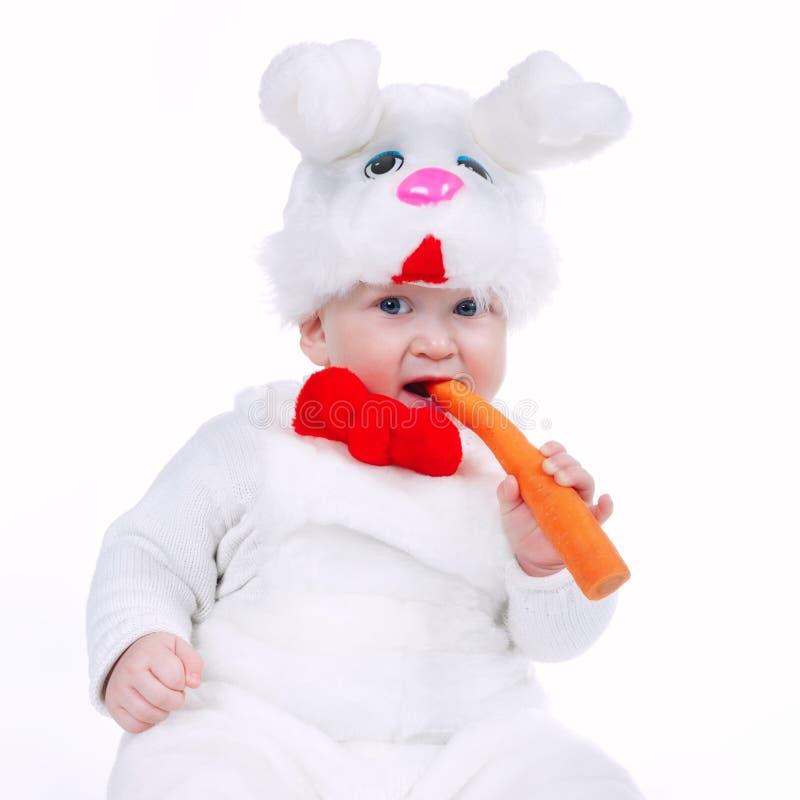 Weinig jongen in geïsoleerde konijnkostuum met wortel royalty-vrije stock foto