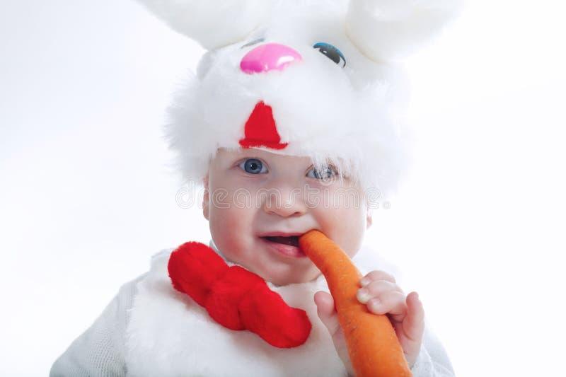 Weinig jongen in geïsoleerde konijnkostuum met wortel stock afbeeldingen