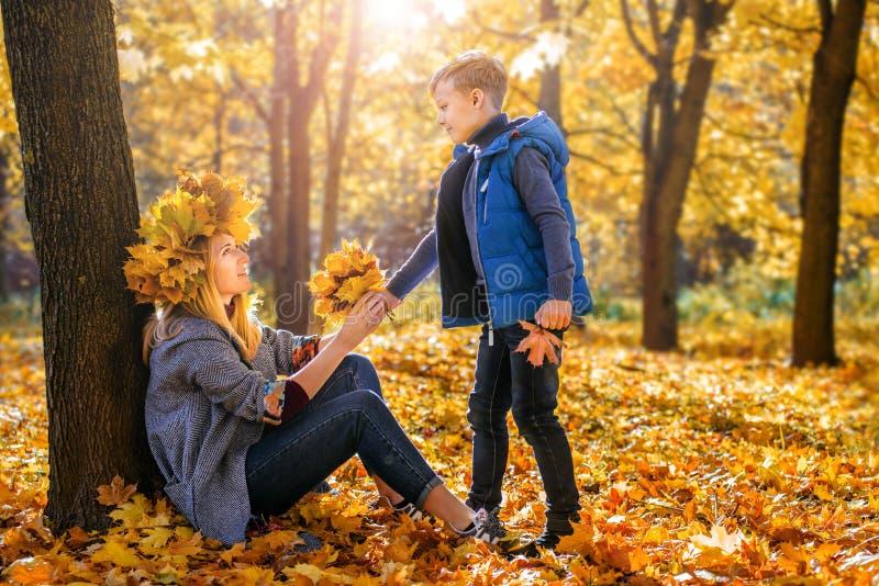 Weinig jongen geeft zijn geliefde moeder een boeket van gele de herfstbladeren royalty-vrije stock afbeeldingen
