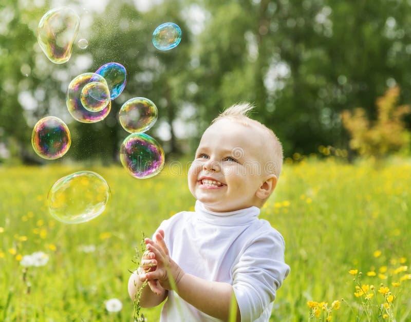 Weinig jongen is gelukkige multi-colored zeepbels royalty-vrije stock foto's