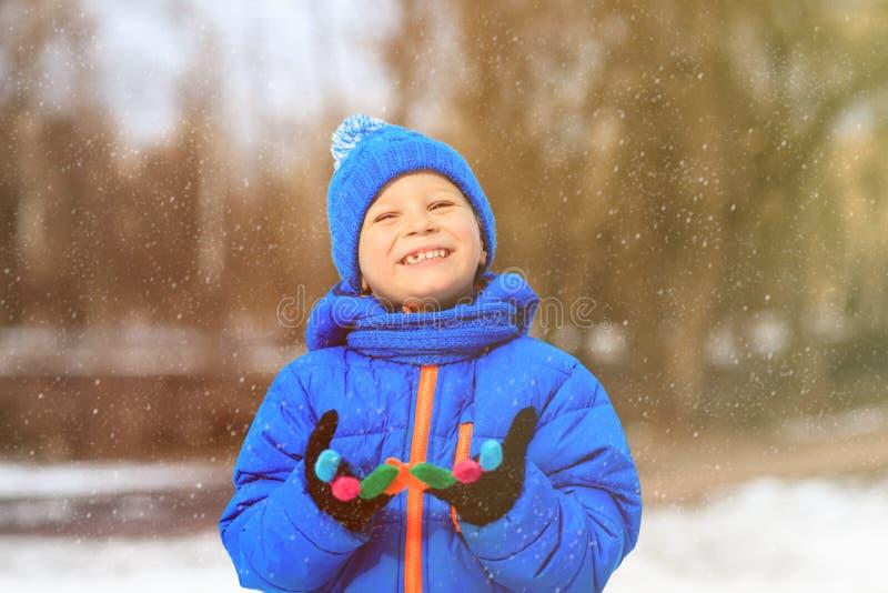 Weinig jongen geniet van eerste sneeuw in de winteraard royalty-vrije stock foto's