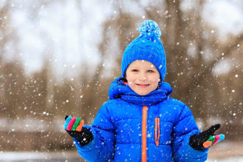 Weinig jongen geniet van eerste sneeuw in de winteraard stock afbeelding