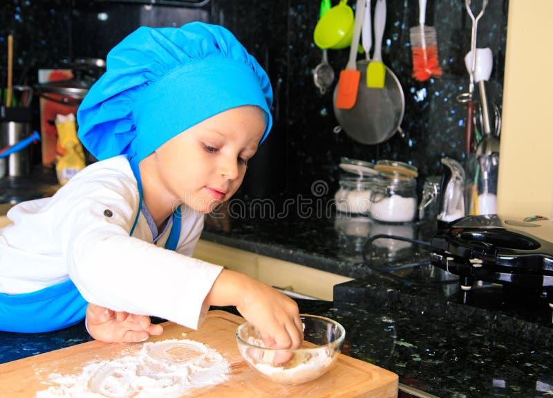 Weinig jongen geniet van kokend in keuken stock foto's