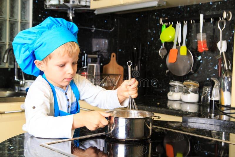 Weinig jongen geniet van kokend in keuken stock foto