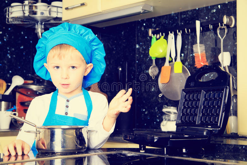 Weinig jongen geniet van kokend in keuken stock afbeelding