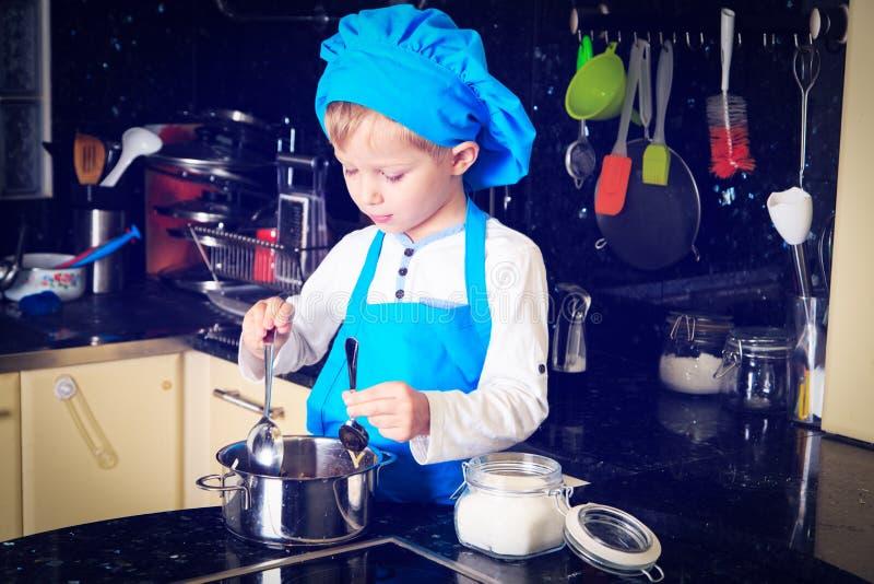 Weinig jongen geniet van kokend in keuken stock afbeeldingen