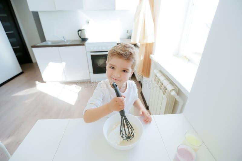 Weinig jongen geniet van kokend in keukenbinnenland stock afbeeldingen