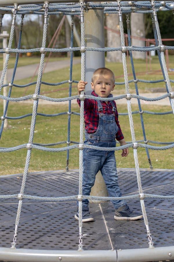Weinig jongen in GLB beklimt op wildernisgymnastiek bij park royalty-vrije stock foto's