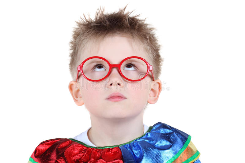 Weinig jongen in groot glazen en clownkostuum kijkt omhoog royalty-vrije stock foto's