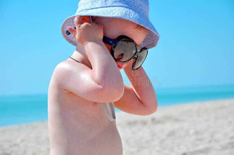 Weinig jongen heeft op moeder` s glazen gezet stock fotografie