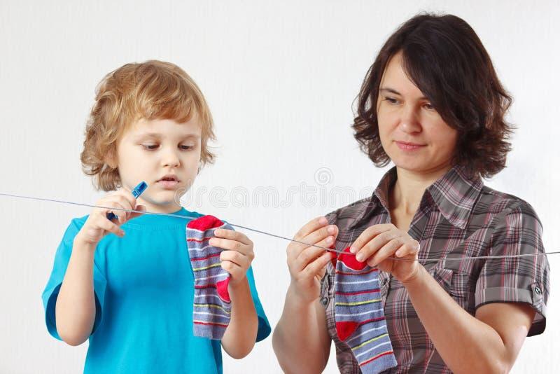 Weinig jongen helpt haar moeder om uw sokken omhoog te hangen stock afbeelding
