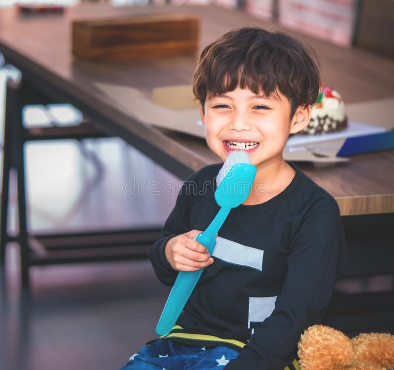 Weinig jongen het borstelen tanden met reuzetandenborstel royalty-vrije stock afbeelding