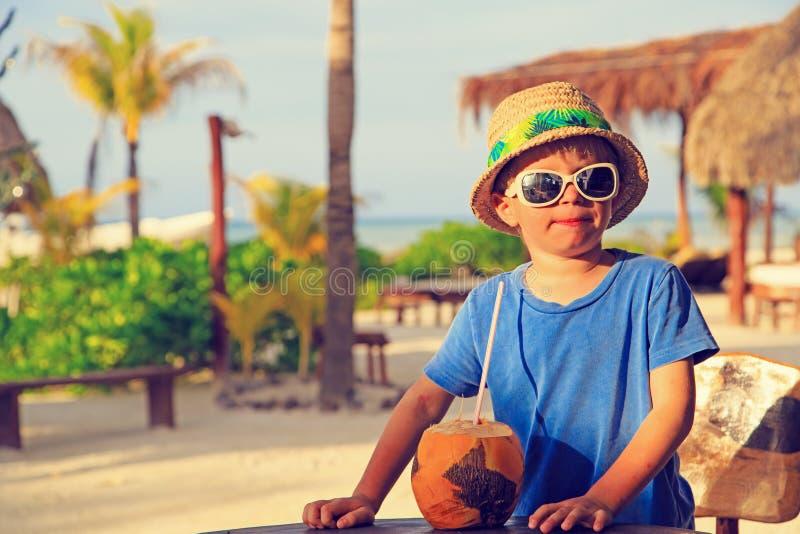 Weinig jongen het drinken kokosnotencocktail op strand royalty-vrije stock foto