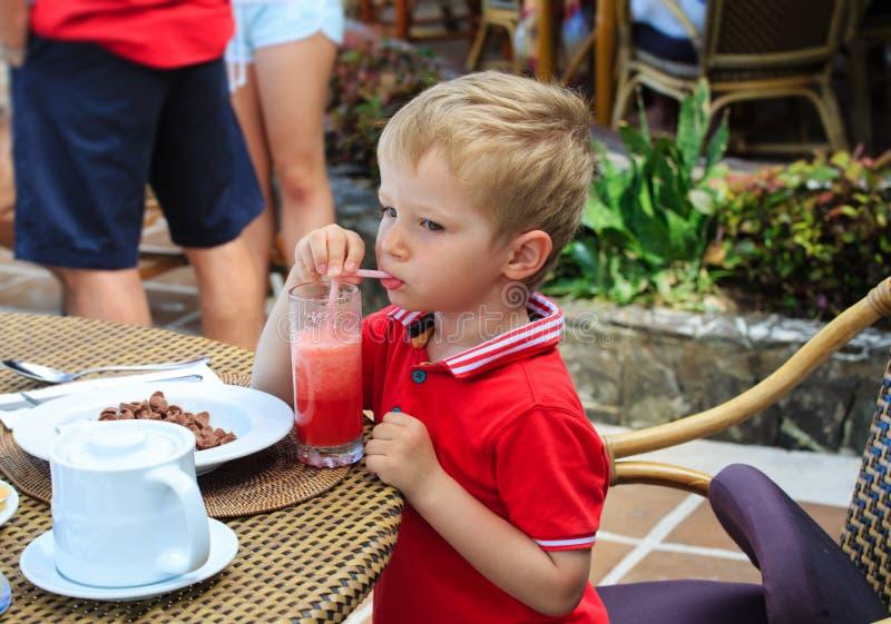 Weinig jongen het drinken sap in koffie stock foto