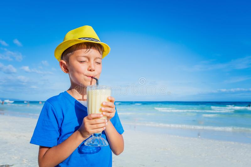 Weinig jongen het drinken sap op tropisch de zomerstrand royalty-vrije stock afbeeldingen