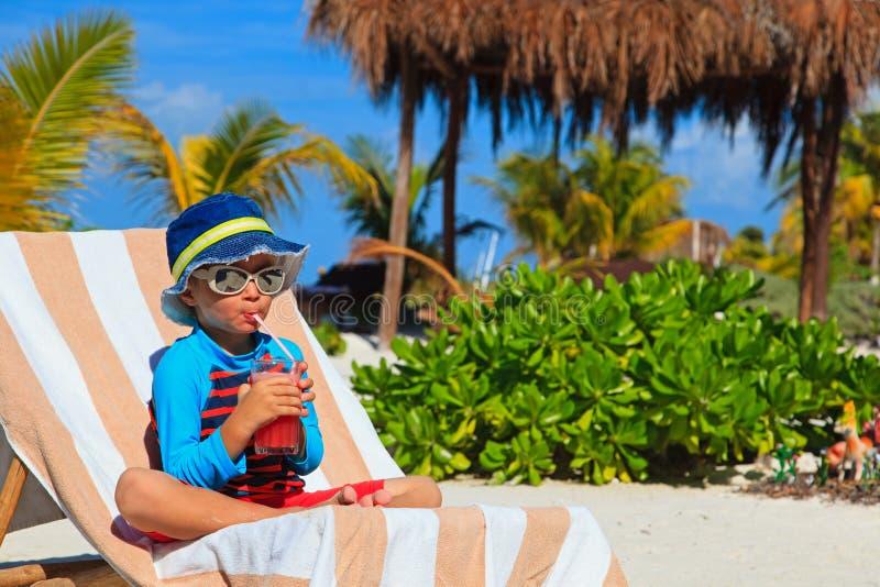 Weinig jongen het drinken sap op tropisch strand royalty-vrije stock foto's