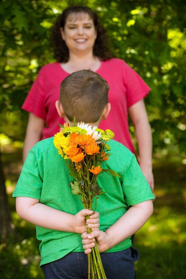 Weinig jongen het geven bloeit aan zijn mamma stock foto's