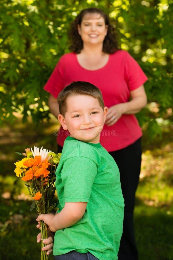 Weinig jongen het geven bloeit aan zijn mamma royalty-vrije stock foto