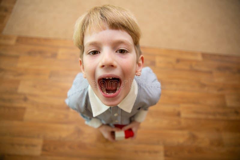 Weinig jongen het gillen Jongen met open mond stock afbeelding