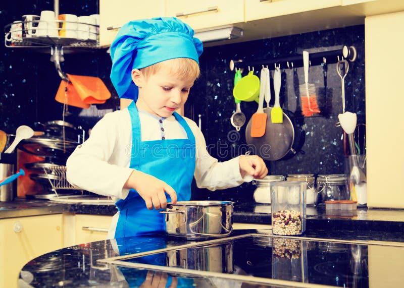 Weinig jongen het koken in keukenbinnenland royalty-vrije stock afbeeldingen