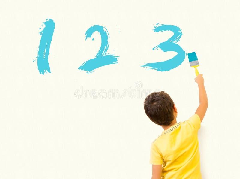 Weinig jongen het leren wiskunde en het schilderen nummer 123 op de muur royalty-vrije stock afbeelding