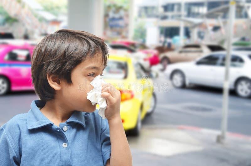 Weinig jongen het niezen oorzaak allergisch op de weg stock foto