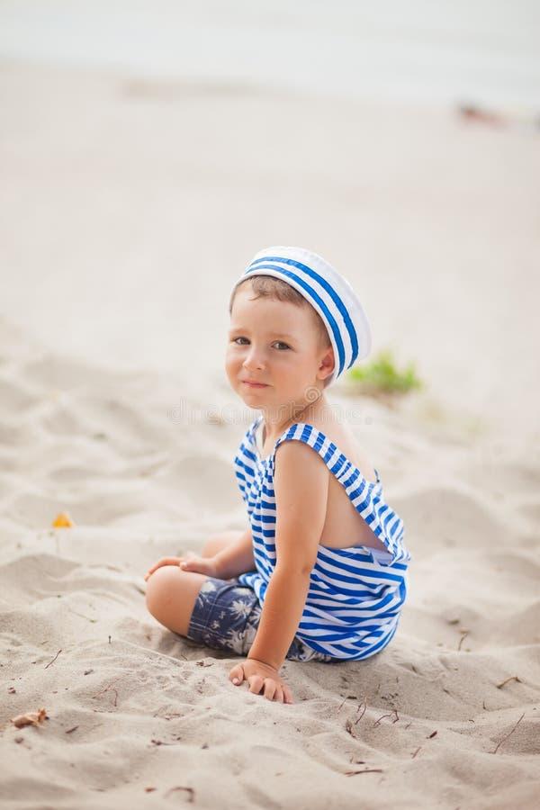 Weinig jongen in het onderhemd en GLB van de zeeman zit op het overzeese strand stock afbeelding