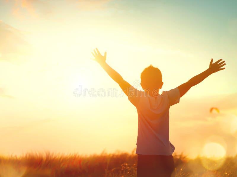 Weinig jongen het opheffen overhandigt zonsonderganghemel royalty-vrije stock foto