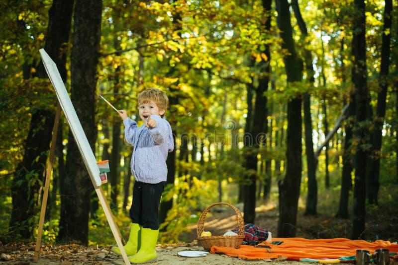 Weinig jongen het schilderen beeld in aard Kunst en zelfuitdrukking Talentenontwikkeling Het schilderen vaardigheden Rust en hobb royalty-vrije stock foto's