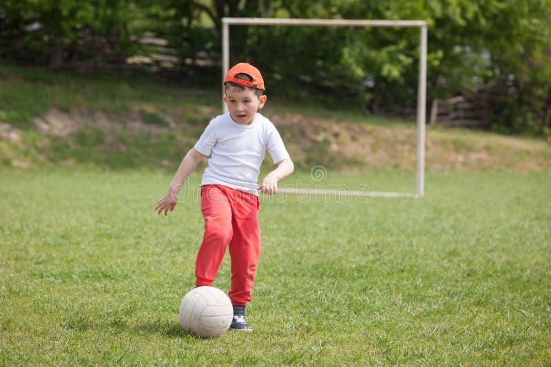 Weinig jongen het schoppen bal in het park speelvoetbalvoetbal in het park sporten voor oefening en activiteit royalty-vrije stock foto