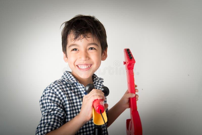 Weinig jongen het spelen gitaar en zingt met microfoon stock foto