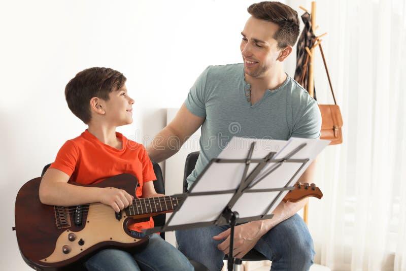 Weinig jongen het spelen gitaar met zijn leraar bij muziekles royalty-vrije stock foto's