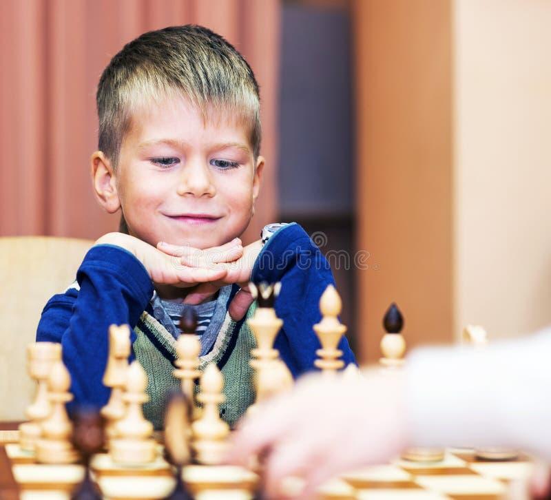 Weinig jongen het spelen schaak stock foto