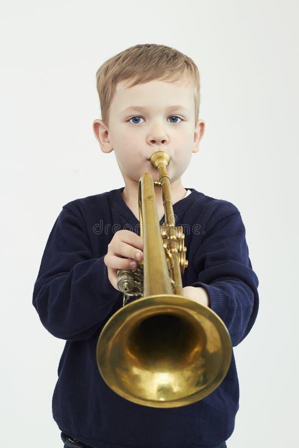 Weinig jongen het spelen trompet muziekkind Muzikaal instrument royalty-vrije stock foto