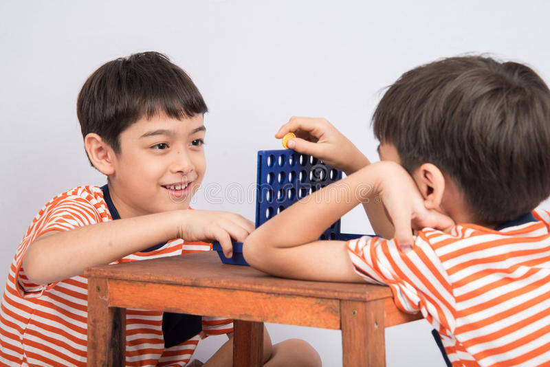 Weinig jongen het spelen verbindt vier spel zachte nadruk bij de binnenactiviteiten van het oogcontact stock fotografie