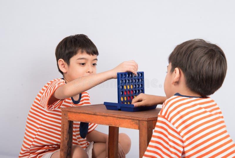 Weinig jongen het spelen verbindt vier spel zachte nadruk bij de binnenactiviteiten van het oogcontact stock foto