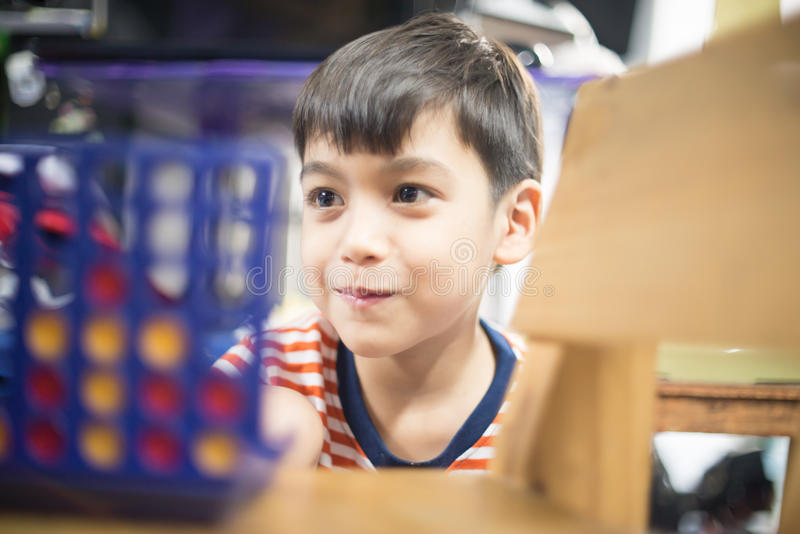 Weinig jongen het spelen verbindt vier spel zachte nadruk bij oogcontact stock afbeeldingen