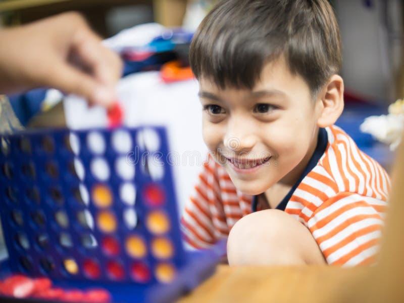 Weinig jongen het spelen verbindt vier spel zachte nadruk bij oogcontact stock foto