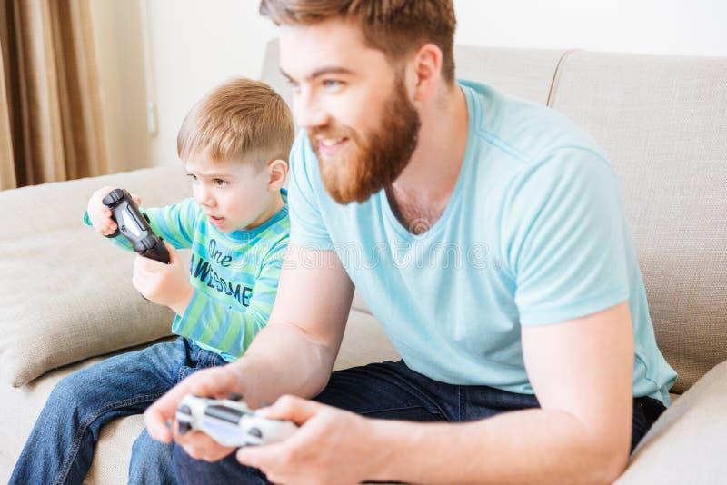 Weinig jongen het spelen videospelletjes met papazitting op bank stock foto's
