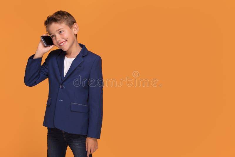 Weinig jongen het stellen met mobiele telefoon stock foto's