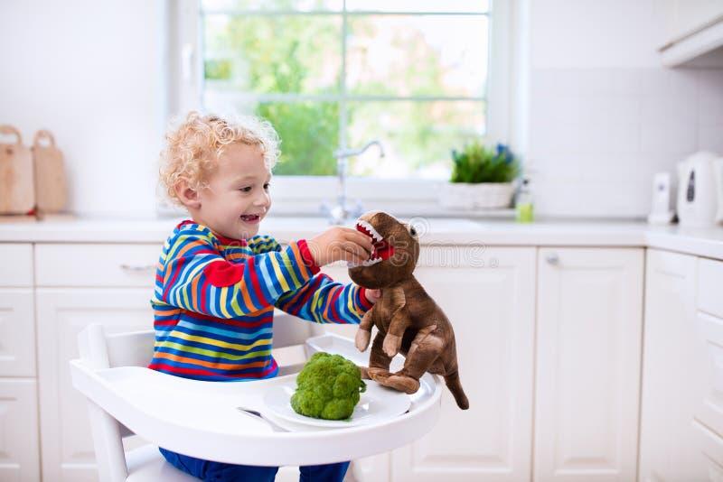 Weinig jongen het voeden broccoli aan stuk speelgoed dinosaurus stock foto's