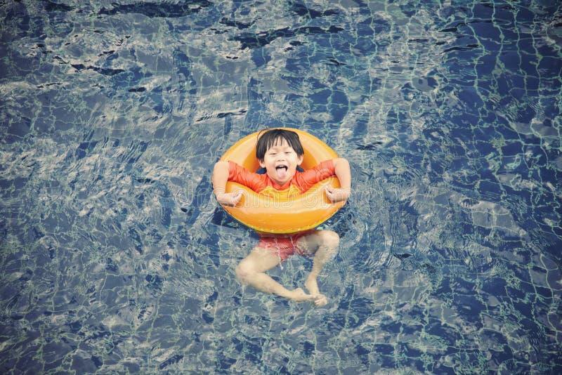 Weinig jongen in het zwembad met rubberring stock foto