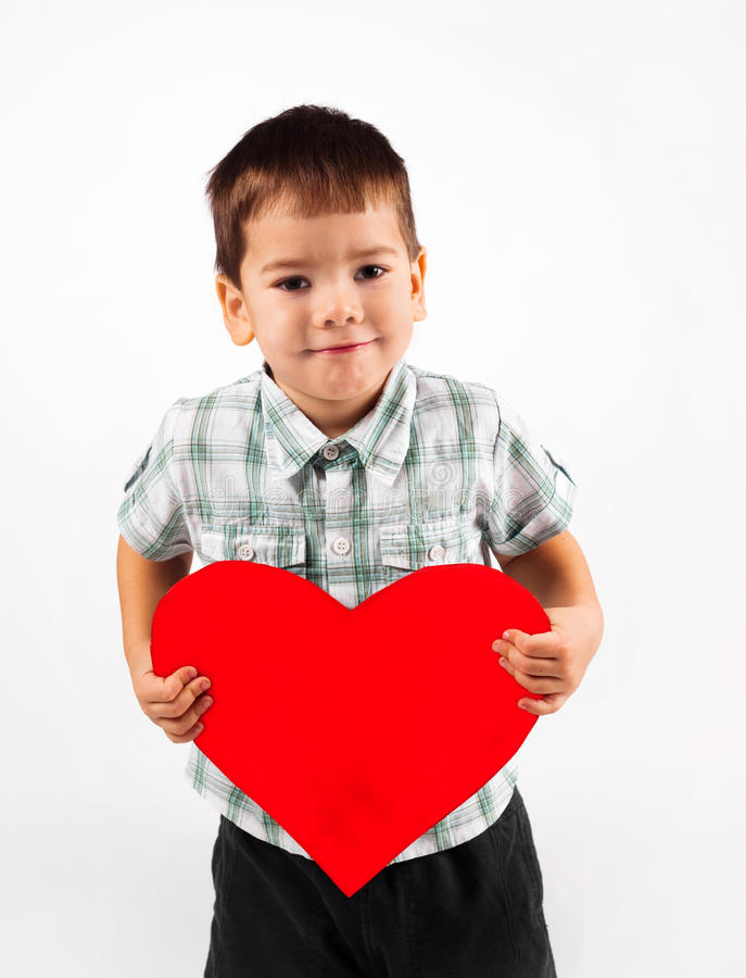 Weinig jongen houdt een groot rood hart stock foto