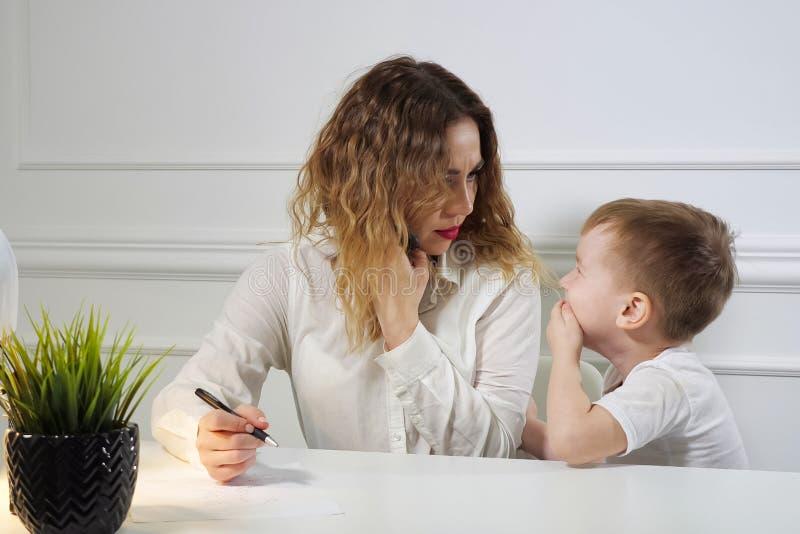 Weinig jongen houdt zijn mamma tegen om te werken terwijl zij telefoon in haar werkplaats in bureau roept Werkende moeder stock afbeelding