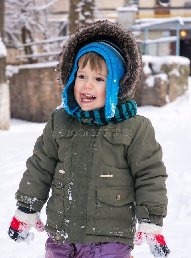 Weinig jongen in jasje en gebreide hoed die sneeuwvlokken in de winterpark vangen op Kerstmis royalty-vrije stock foto