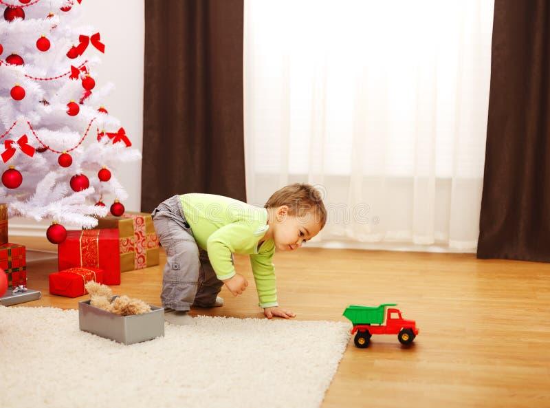 Weinig jongen in Kerstmis, die met nieuwe stuk speelgoed auto speelt stock afbeelding
