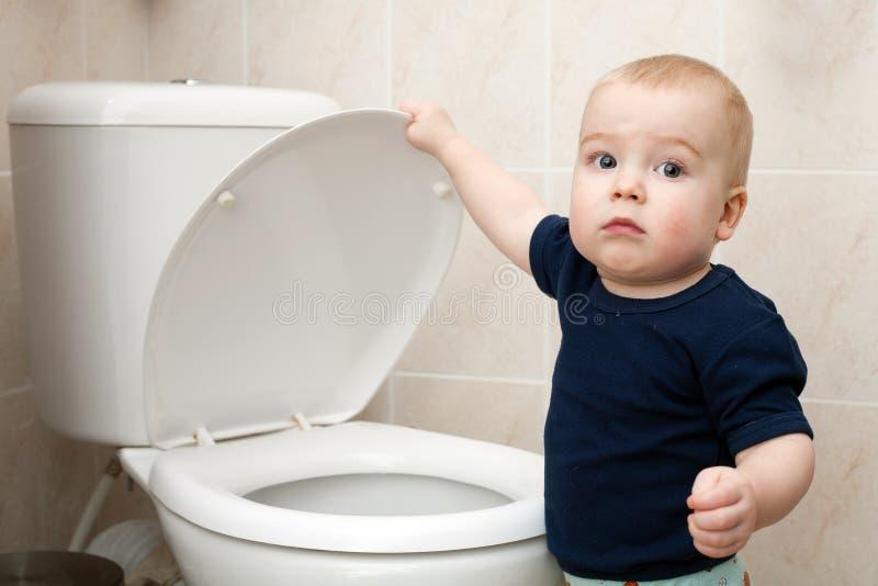 Weinig jongen kijkt in het toilet stock foto's