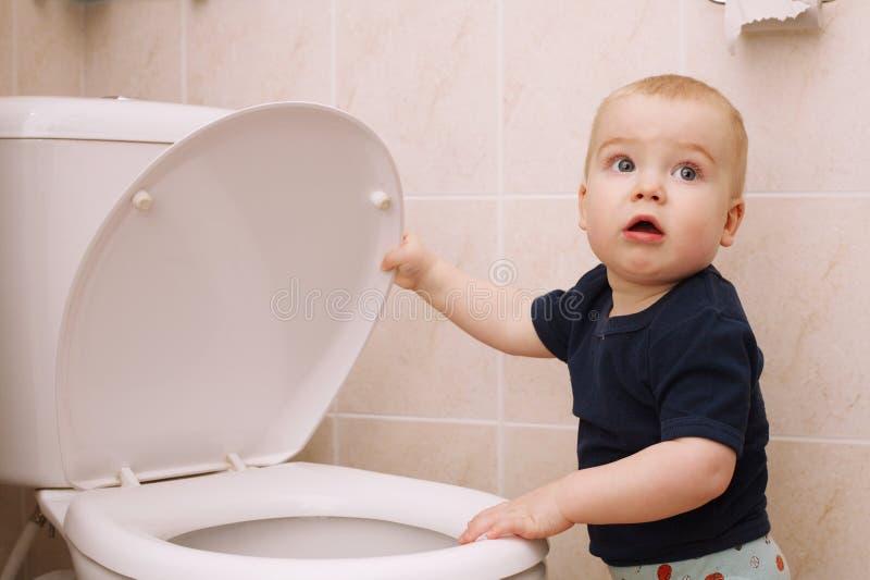 Weinig jongen kijkt in het toilet royalty-vrije stock afbeelding