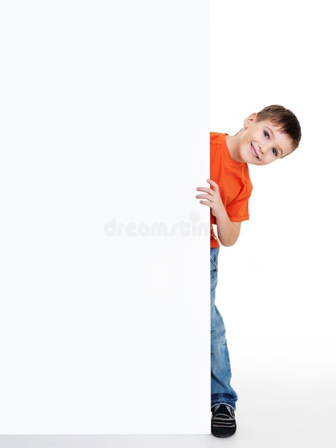 Weinig jongen kijkt outs van het lege aanplakbord royalty-vrije stock foto