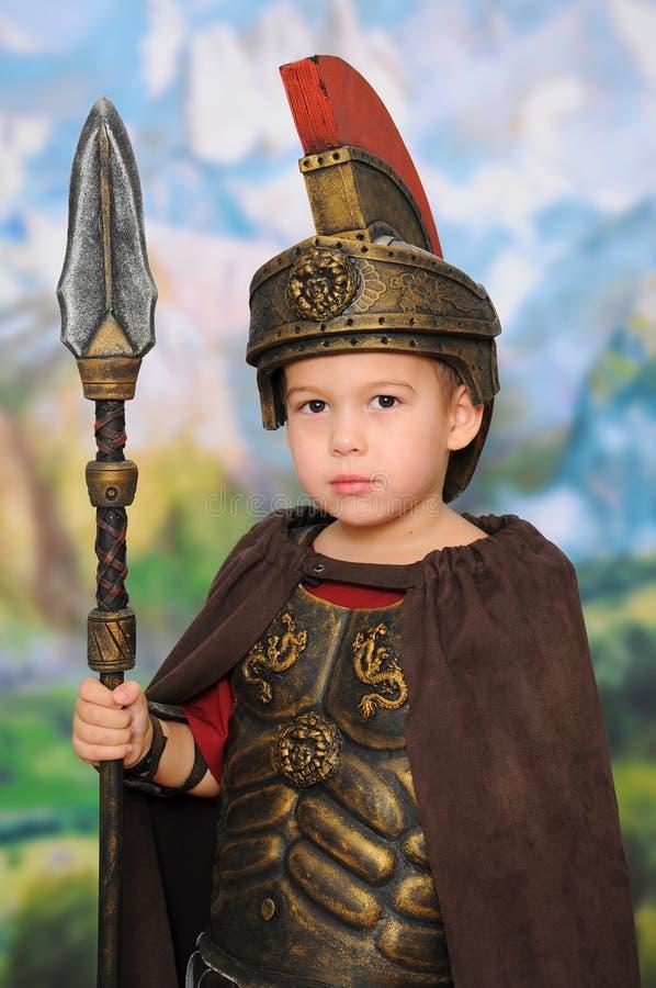Weinig jongen kleedde zich als Roman militair stock afbeeldingen